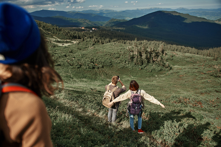 Top view with focus on man and woman standing on mount slope and observing landscape in front. Guy holding smartphone for taking picture of view and lady is spreading arms with excitement