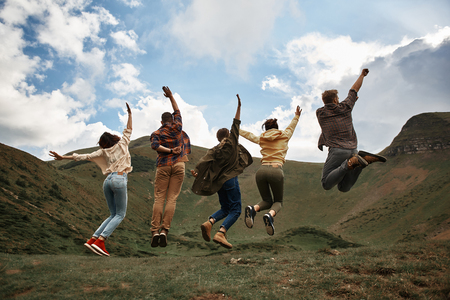Lets jump. Excited young hikers having fun and jumping while being in the mountains