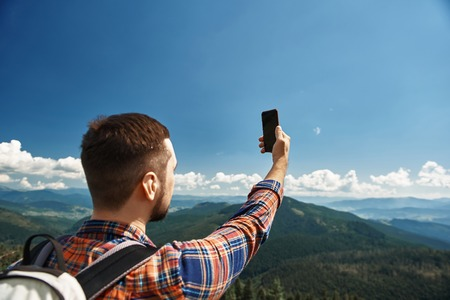 Guy standing high on peak and lifting arm. He holding smartphone and taking picture among beautiful scenery
