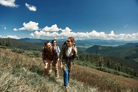 Cheerful man and two women hiking in mountains. They are travelling with rucksacks together along path up to top