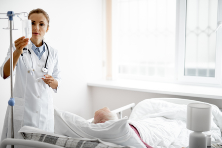 Portrait of young woman in white lab coat checking intravenous drip while old man lying in bed. Copy space on right side