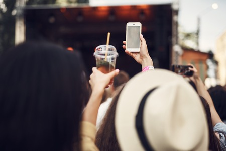 Close up of female hands holding cellphone and cup with mint beverage.