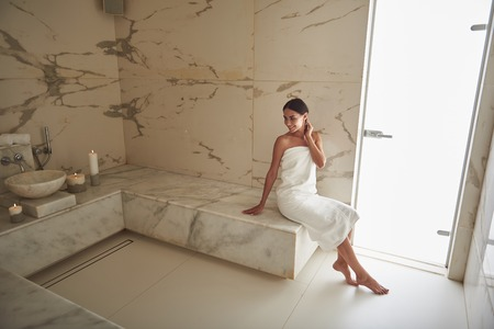Cheerful attractive young woman smiling and turning back while wearing white towel and sitting on the marble surface