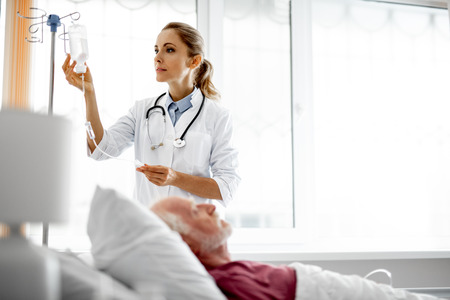 Waist up portrait of young woman in white lab coat checking intravenous drip in hospital room. Blurred old man lying in bed