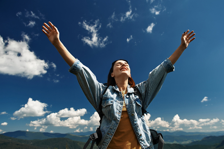 Low angle of smiling woman standing under blue sky and raising arms with enjoyment. 스톡 콘텐츠