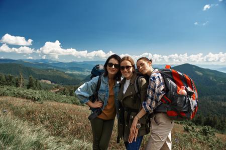 Waist up portrait of three smiling women exploring mountainous landscapes together. Banco de Imagens