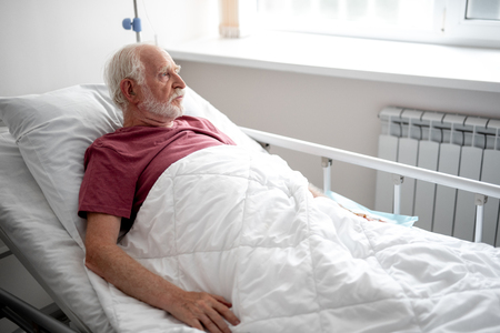 Waiting for doctor. Side view portrait of serious old man resting in recovery room Stock Photo - 110952273