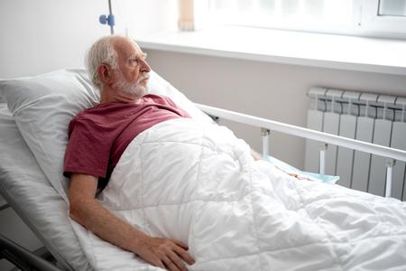 Warten auf Arzt. Seitenansichtporträt eines ernsten alten Mannes, der im Aufwachraum ruht Standard-Bild