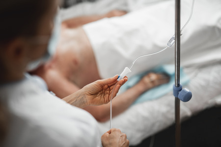 Close up of female hands regulating IV infusion by using a roller clamp.
