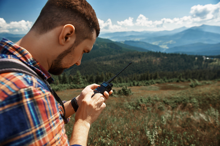 Focus on guy holding walkie-talkie and trying to find connection. He is standing with gadget while travelling through mountains Stock Photo
