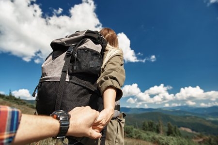 Low angle of woman with rucksack climbing mountain and holding man by hand.