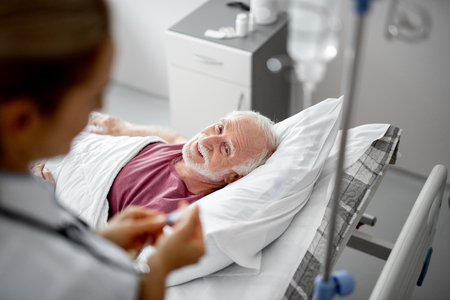 Portrait of joyful old man lying in hospital bed while female therapist regulating IV infusion. Focus on bearded gentleman