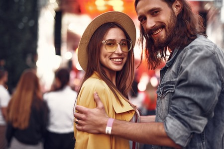 Portrait of handsome bearded man touching shoulders of his charming girlfriend. They looking at camera and smiling