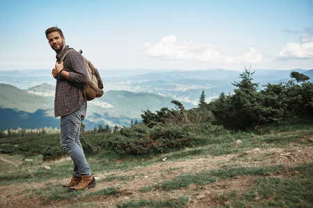 Joyful male walking with backpack in mountains. 스톡 콘텐츠