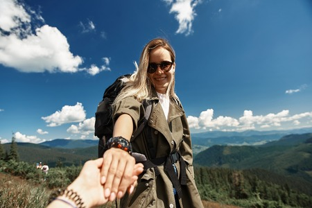 Waist up portrait of cheerful lady enjoying time on mountain top. She is carrying rucksack and wearing sunglasses 스톡 콘텐츠 - 110953214