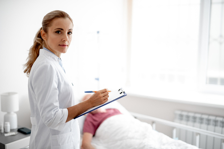 Waist up portrait of beautiful lady in white lab coat holding clipboard and pen. Man lying in bed on blurred background