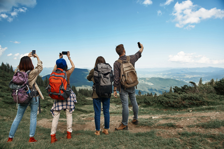 Three women and one man standing with back to camera in highland valley during break in their tour with rucksacks 스톡 콘텐츠 - 110953164
