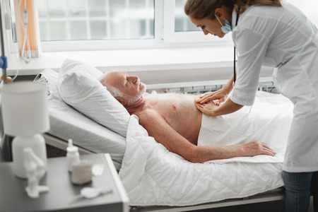 I am feeling sick. Side view portrait of shirtless old man lying in bed during medical examination Stock Photo