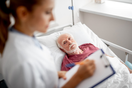 Portrait of old man resting in hospital room and staring at young lady while she writing on clipboard. Focus on bearded gentleman