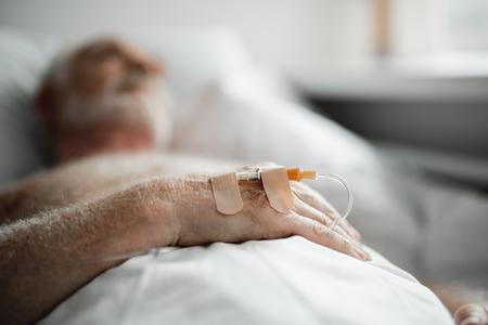Nahaufnahme der männlichen Hand mit IV-Tropf. Alter Mann ruht sich nach der Operation auf unscharfem Hintergrund aus