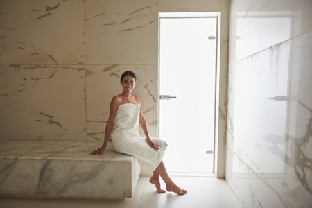 Positive emotional young woman feeling good after hammam procedures and smiling while sitting in white towel on the marble surface
