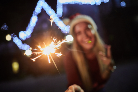 Close up of sparkler in hands of a pleasant happy woman holding it while having fun outdoors