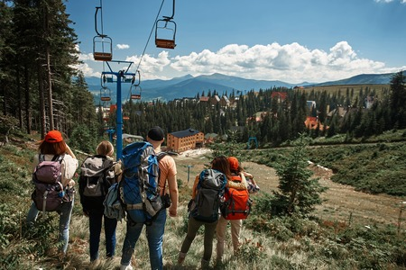 Four women and one man travelling through mountains with rucksacks. They standing with focus on back near chair lift and staring forward at village downhill 스톡 콘텐츠