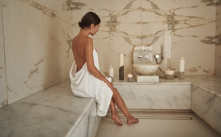 Woman in hammam. Peaceful dark haired lady showing her beautiful legs and looking calm at hammam procedure Stock fotó