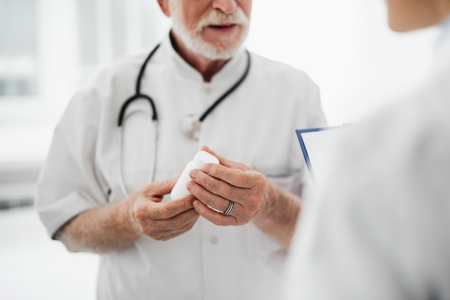 Close up of pharmacy bottle with pills in male hands. Therapist in white lab coat standing on blurred background. Focus on arms Reklamní fotografie