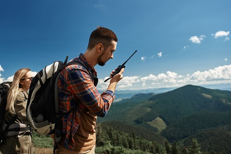 Couple is backpacking in mountains together. They are standing while guy is speaking via walkie-talkie Stock fotó