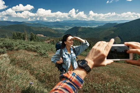 Focus on cheerful lady travelling through mountainous mass with backpack. She is standing and raising hand to forehead for protecting from sun and looking forward 스톡 콘텐츠 - 110953099