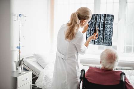 Back view portrait of young lady in white lab coat holding x-ray image and pointing at it while gentleman sitting in wheelchair