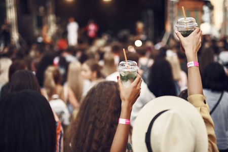 Drink to that. Close up of female hands holding cups with mint beverage. Stage and crowd in blurred background Reklamní fotografie