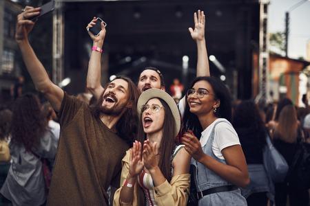 S'amuser. Portrait de taille de jeunes prenant une photo avec un smartphone tout en profitant d'un concert