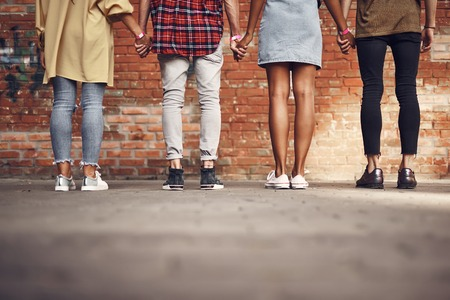 Holding hands. Confident close people in casual clothes standing in front of the brick wall and holding hands Imagens