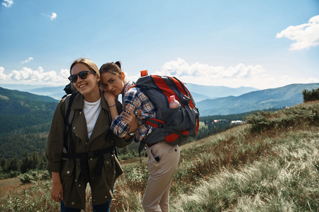Joyful women hiking together with rucksacks among green tops. They standing and embracing while having great time 写真素材