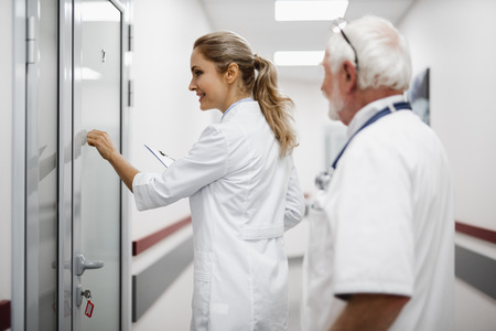 Side view portrait of beautiful young lady in white lab coat holding clipboard and planning to visit patient.