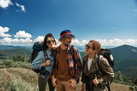 Smiling two women and man backpacking together in mountainous area.