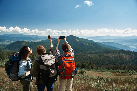 Female friends standing with focus on back and taking picture of amazing peaks scenery in distance while using smartphones