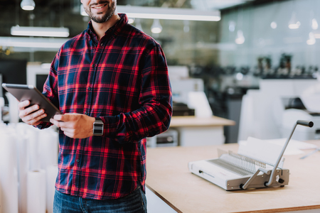 Smiling man standung in modern office and working with gadget