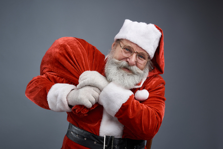 Waist up portrait of bearded old man in Santa costume carrying bag with christmas presents. Isolated on gray background Stock Photo