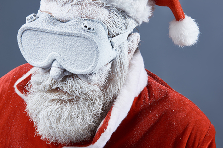Cold weather. Close up portrait of frozen old man in Santa costume wearing protective glasses and looking down