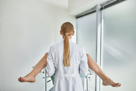 Relax and do not worry. Back view portrait of female gynecologist during pelvic exam