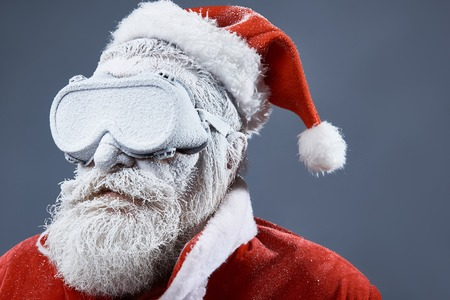 Close up portrait of frozen old man in Santa costume wearing protective glasses and looking away