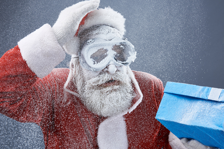Portrait of bearded old man in Santa costume covered with snow holding blue gift box. He is wearing protective glasses Banco de Imagens