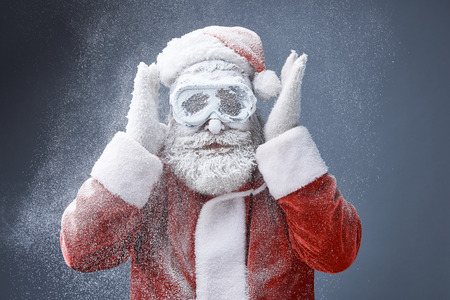 Christmas snowstorm. Portrait of bearded old man in Santa costume standing under snow Imagens