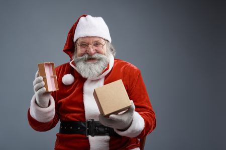 Waist portrait of bearded old man in Santa costume posing with christmas present on gray background. He looking at camera and smiling
