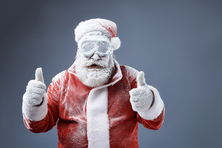 Portrait of bearded old man in Santa costume covered with snow demonstrating approval gesture. Isolated on gray-blue background