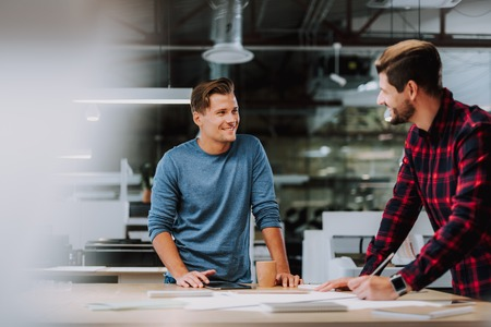 Waist up portrait of two men working on graphic drawing in cabinet and smiling