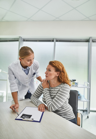 Everything going to be okay. Portrait of gynecologist comforting red-haired woman while she sitting at the table with ultrasound picture